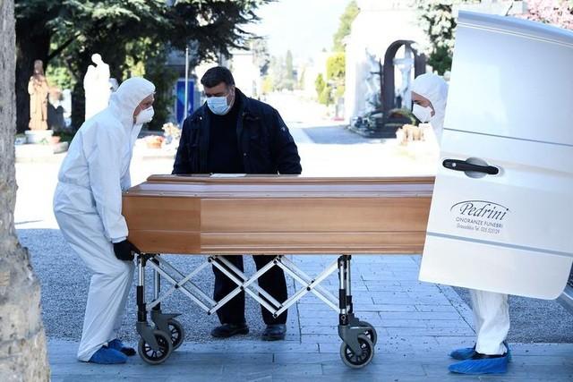 Các nhân viên vận chuyển quan tài của bệnh nhân chết vì Covid-19 tại một nghĩa địa ở Bergamo, Italia (Ảnh: AP)